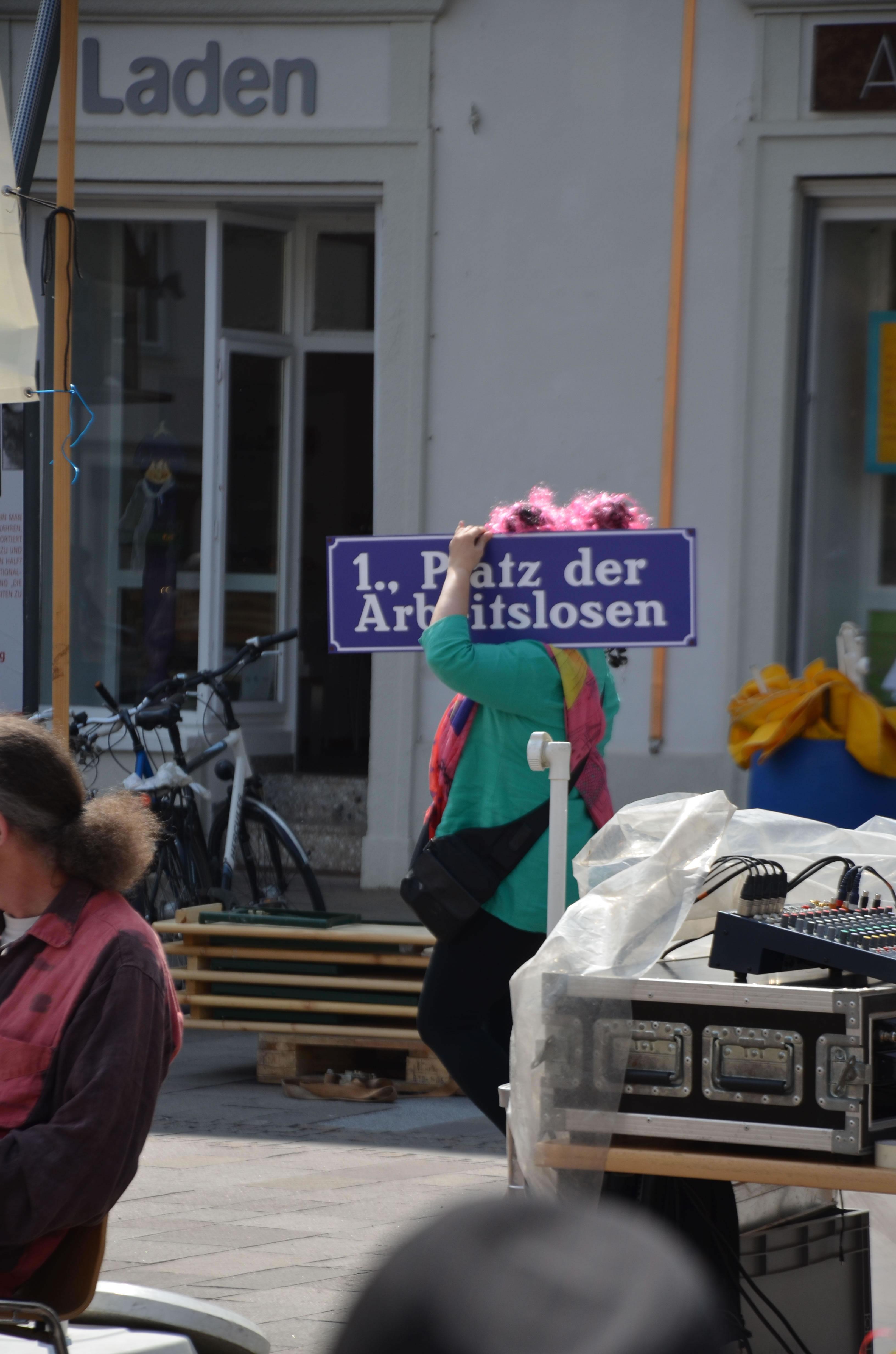 Betty Baloo am Tag der Arbeitslosen 2014 in Graz Mariahilfer Platz mit Schild gehend